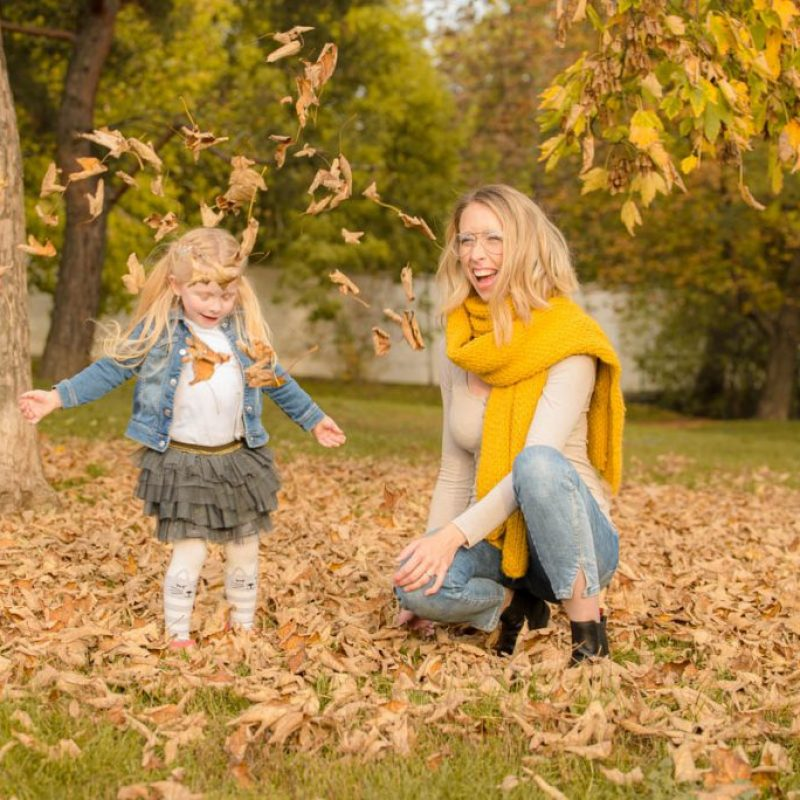 mother and daughter playing with leaves in the park